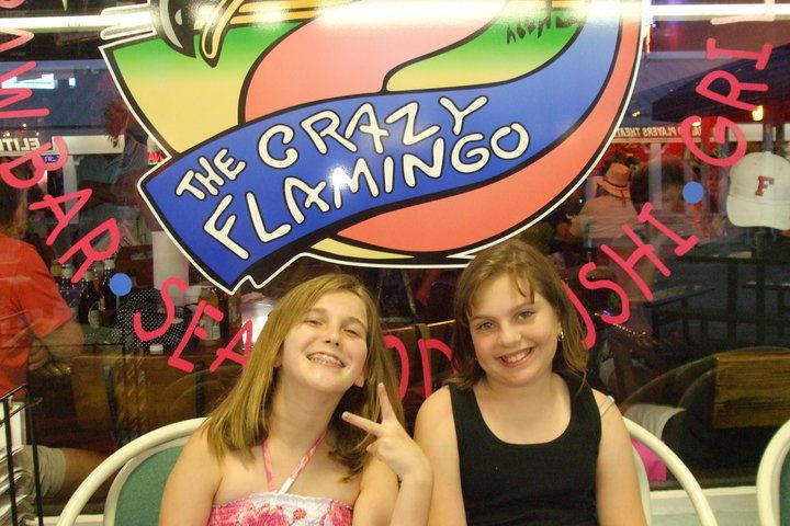 Two kids sitting in front of the Crazy Flamingo sign || Escape to Marco