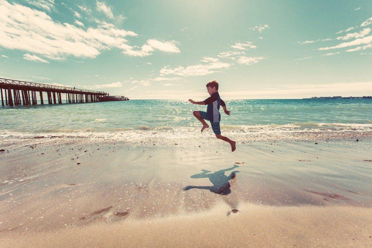 boy skipping on the beach